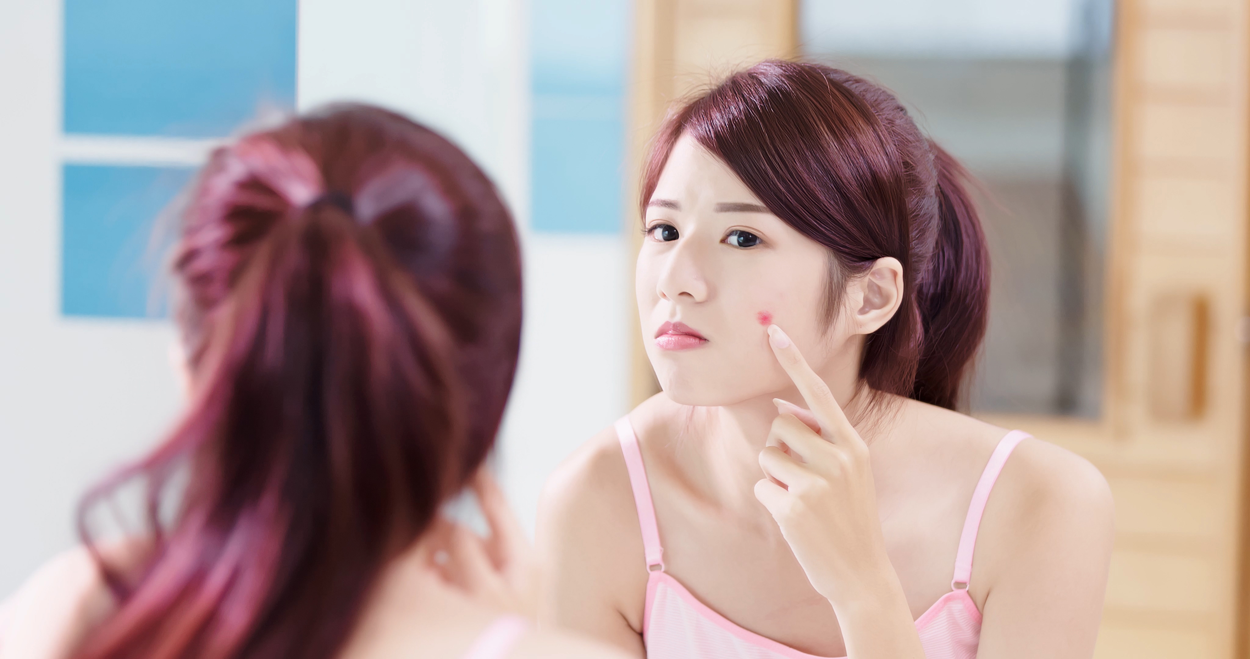 girl with pimple looking in mirror
