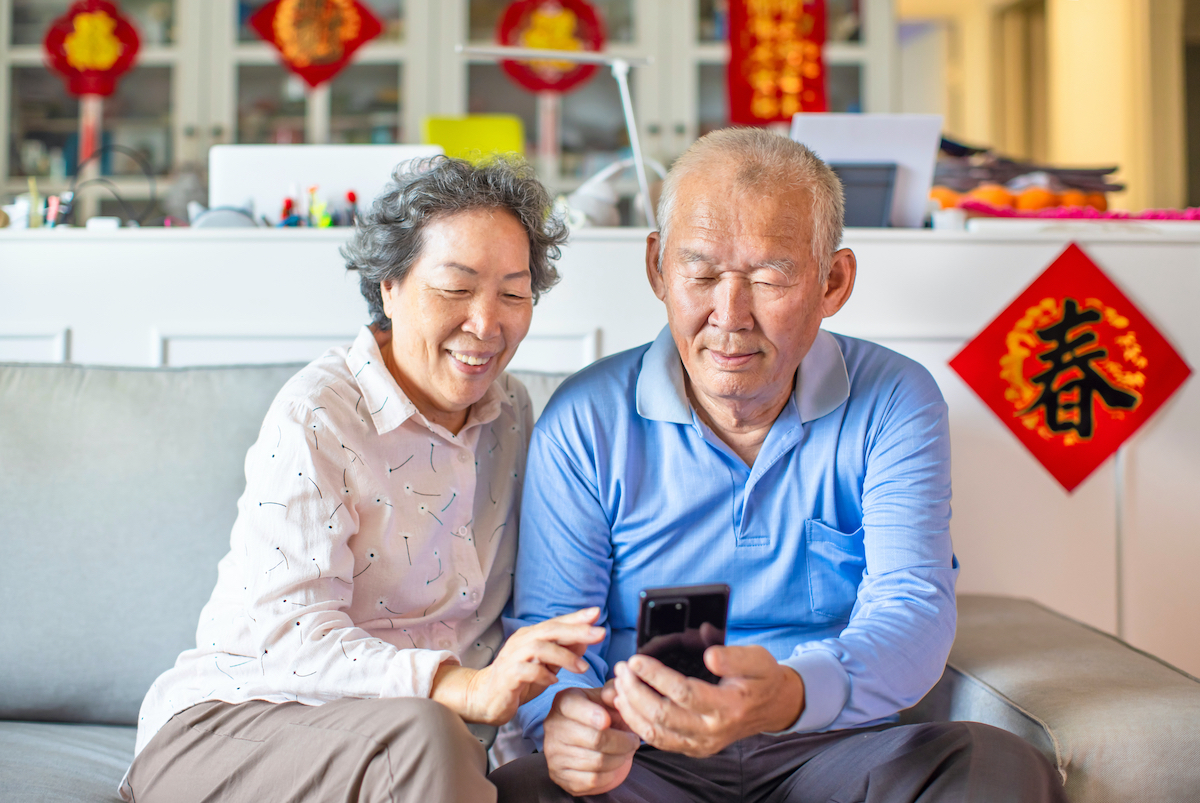 Asian,Senior,Couple,Smiling,And,Looking,At,The,Mobile,Phone